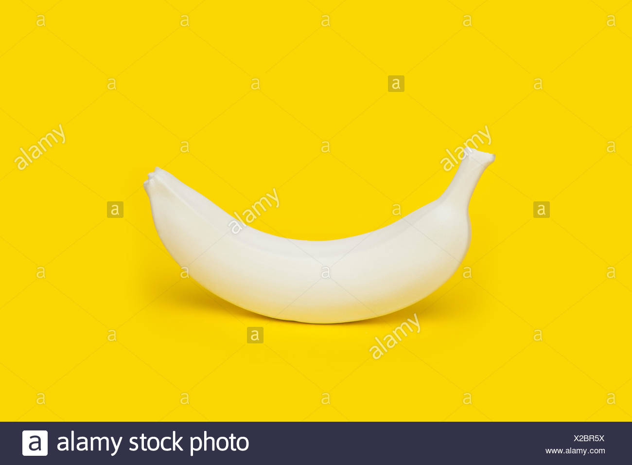 Banana painted white on yellow background - Stock Image