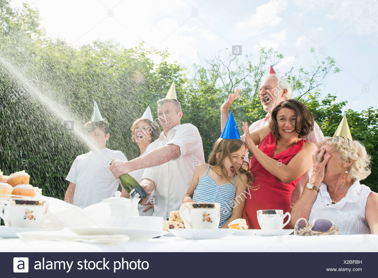 Family celebrating birthday, man opening champagne - Stock Image