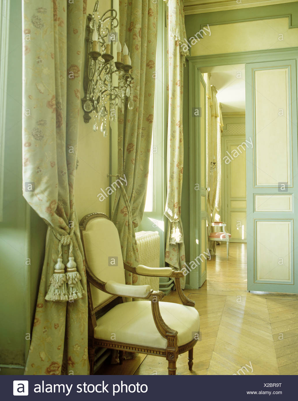 Antique armchair next to opulent curtains with tiebacks in drawing room in French chateau & Antique armchair next to opulent curtains with tiebacks in drawing ...