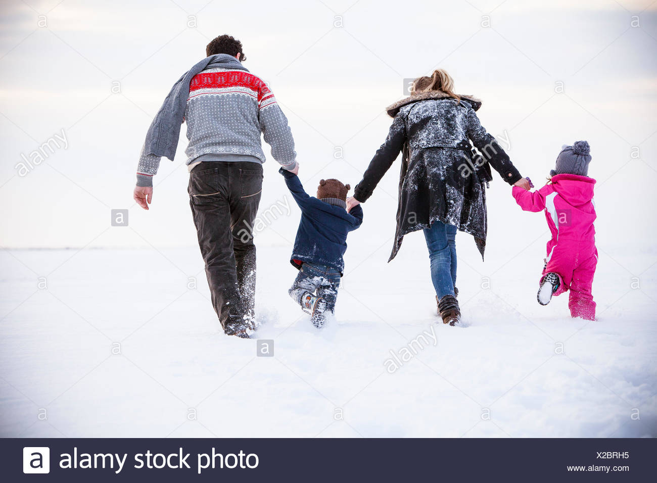 Family walking in snow - Stock Image