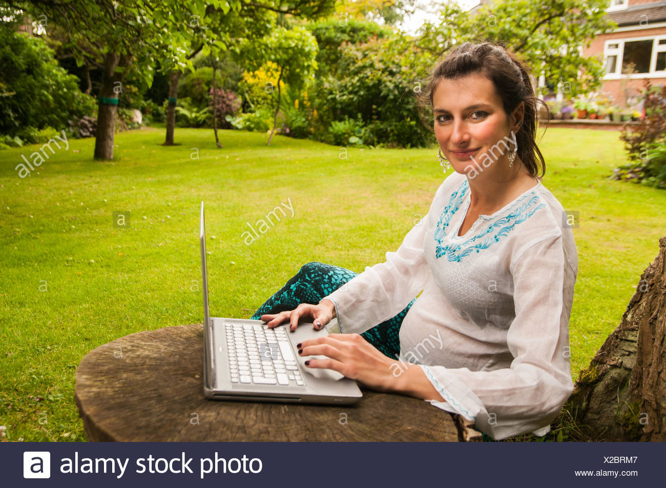 Pregnant woman sitting in garden working on her laptop - Stock Image