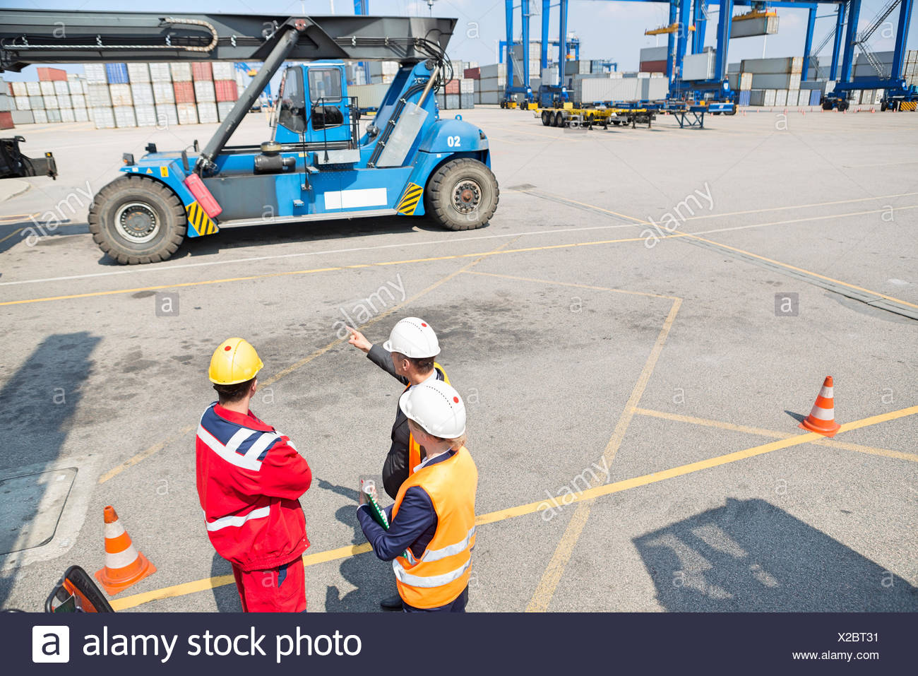 High angle view of workers discussing in shipping yard - Stock Image