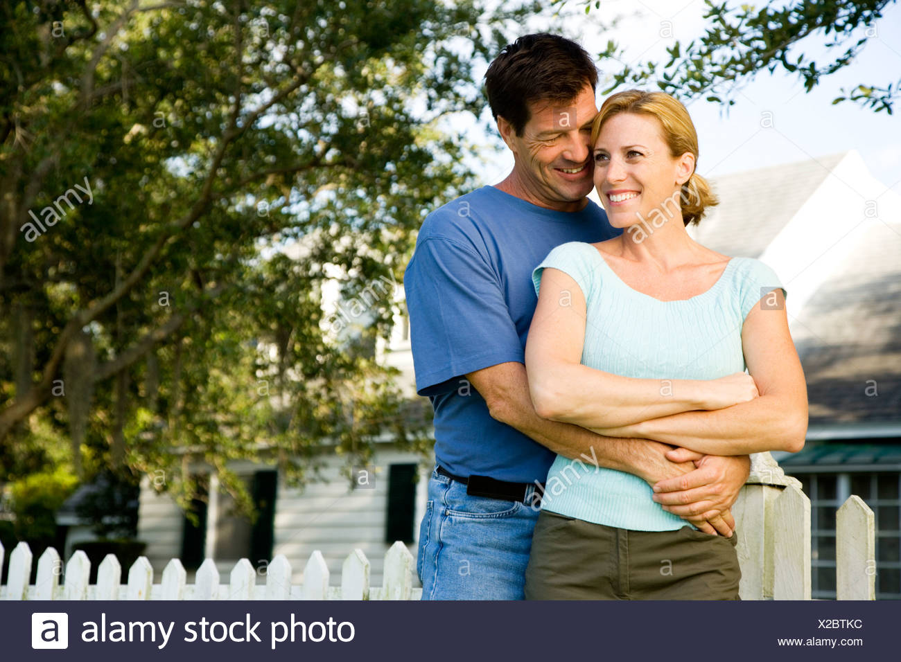 Couple standing by the garden fence outside their new home - Stock Image