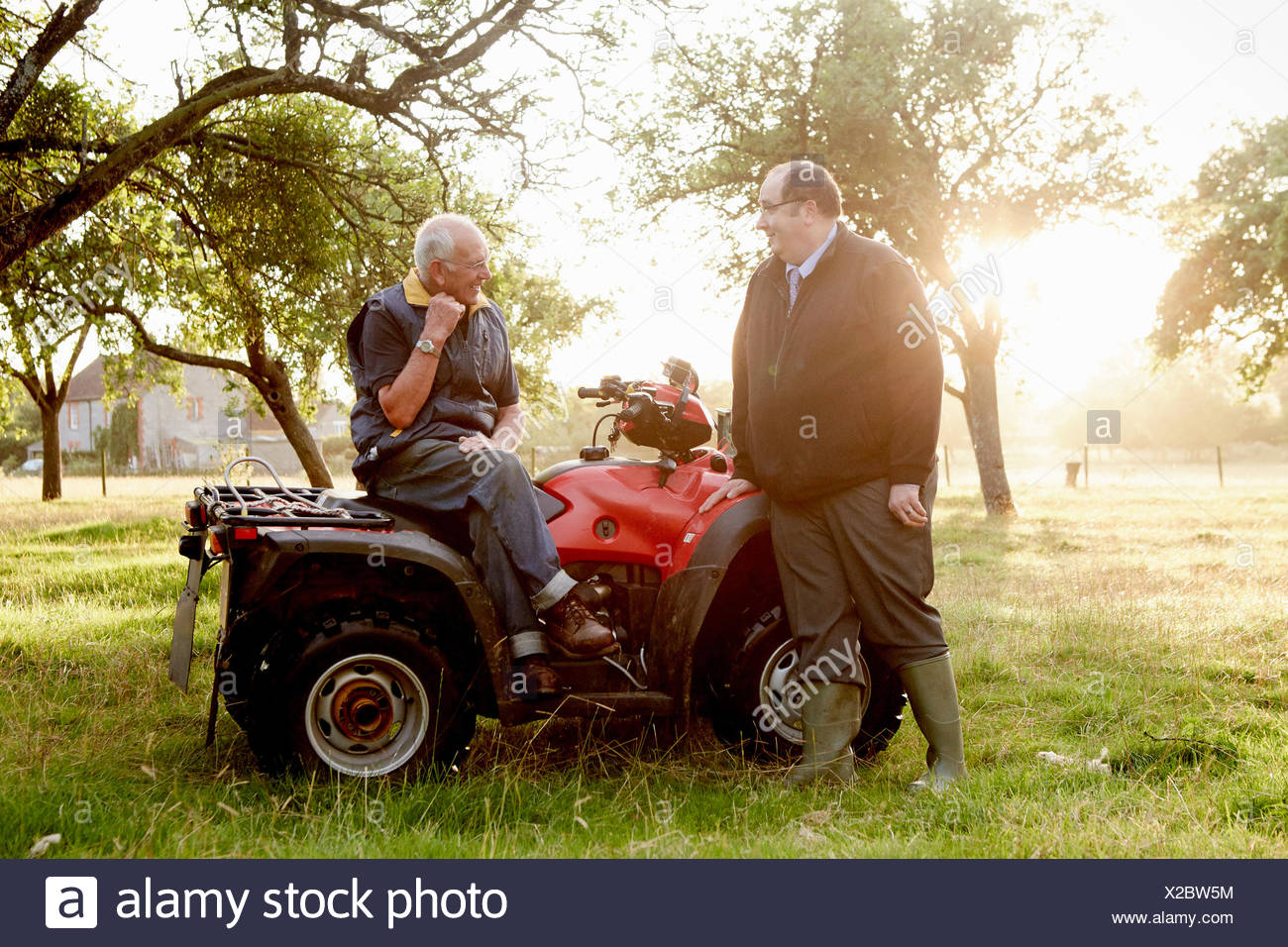 Two men, a farmer and a man with a clipboard, by a quadbike in an orchard. - Stock Image