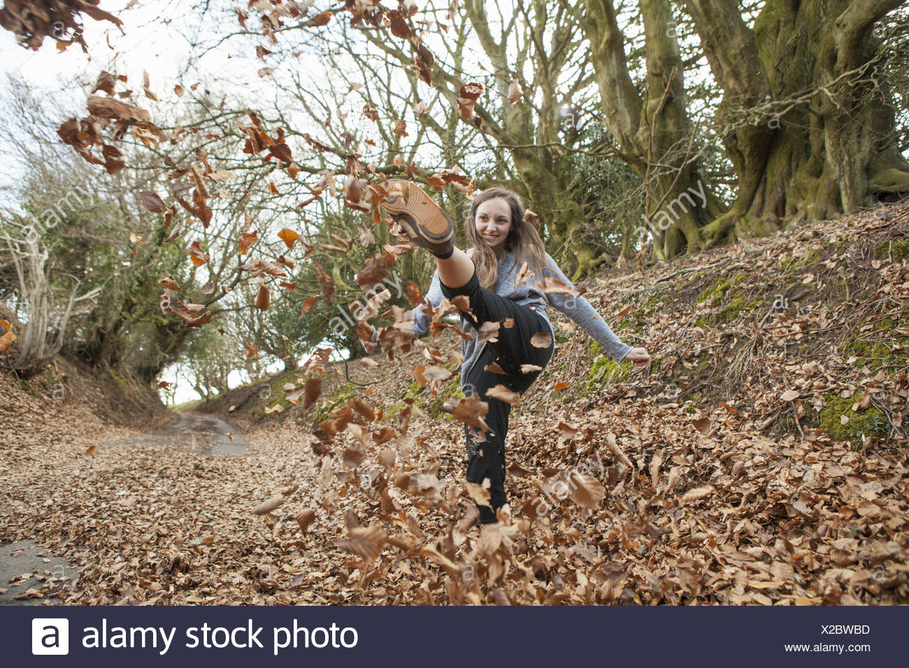 Young woman playing in fallen leaves, kicking them in the air. - Stock Image