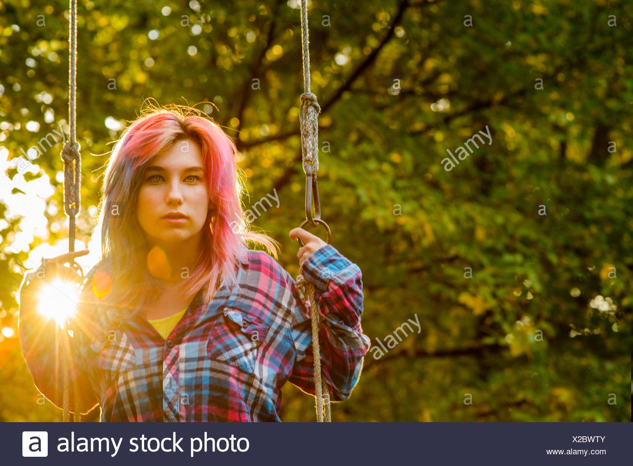 Portrait of teenage girl with multi-coloured hair, on garden swing ...