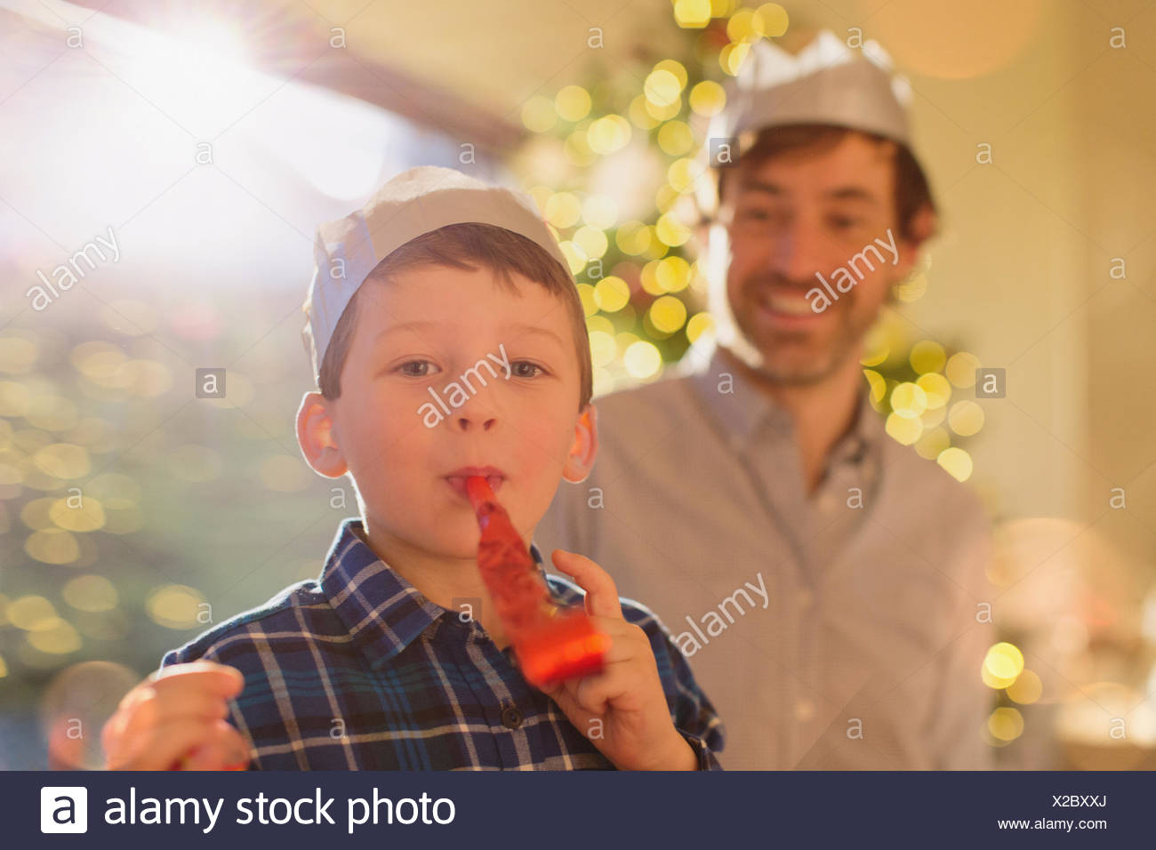 736627bbd7a36 Portrait boy wearing Christmas paper crown blowing party favor - Stock Image
