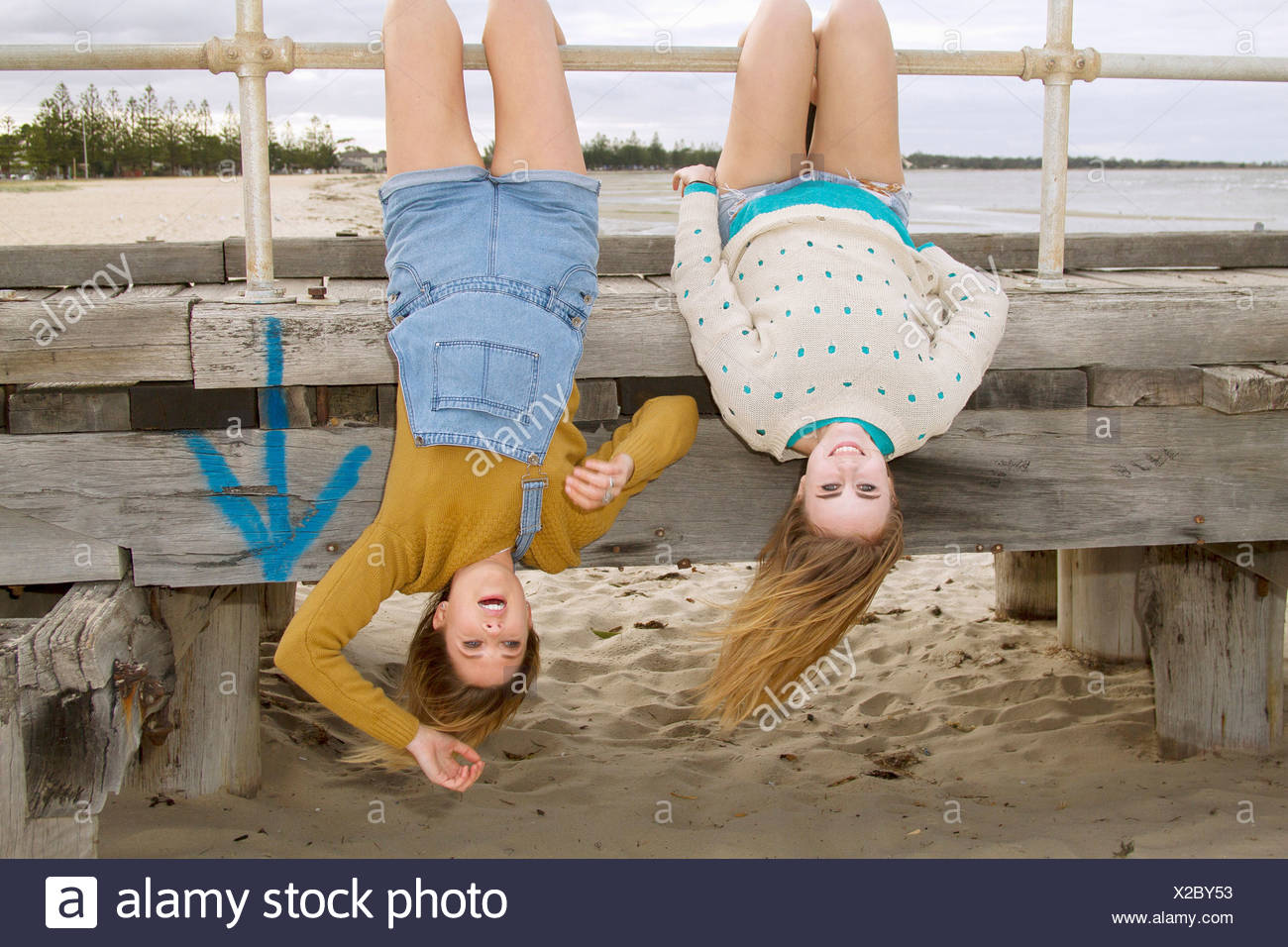 Girlfriends hanging upside down from pier - Stock Image