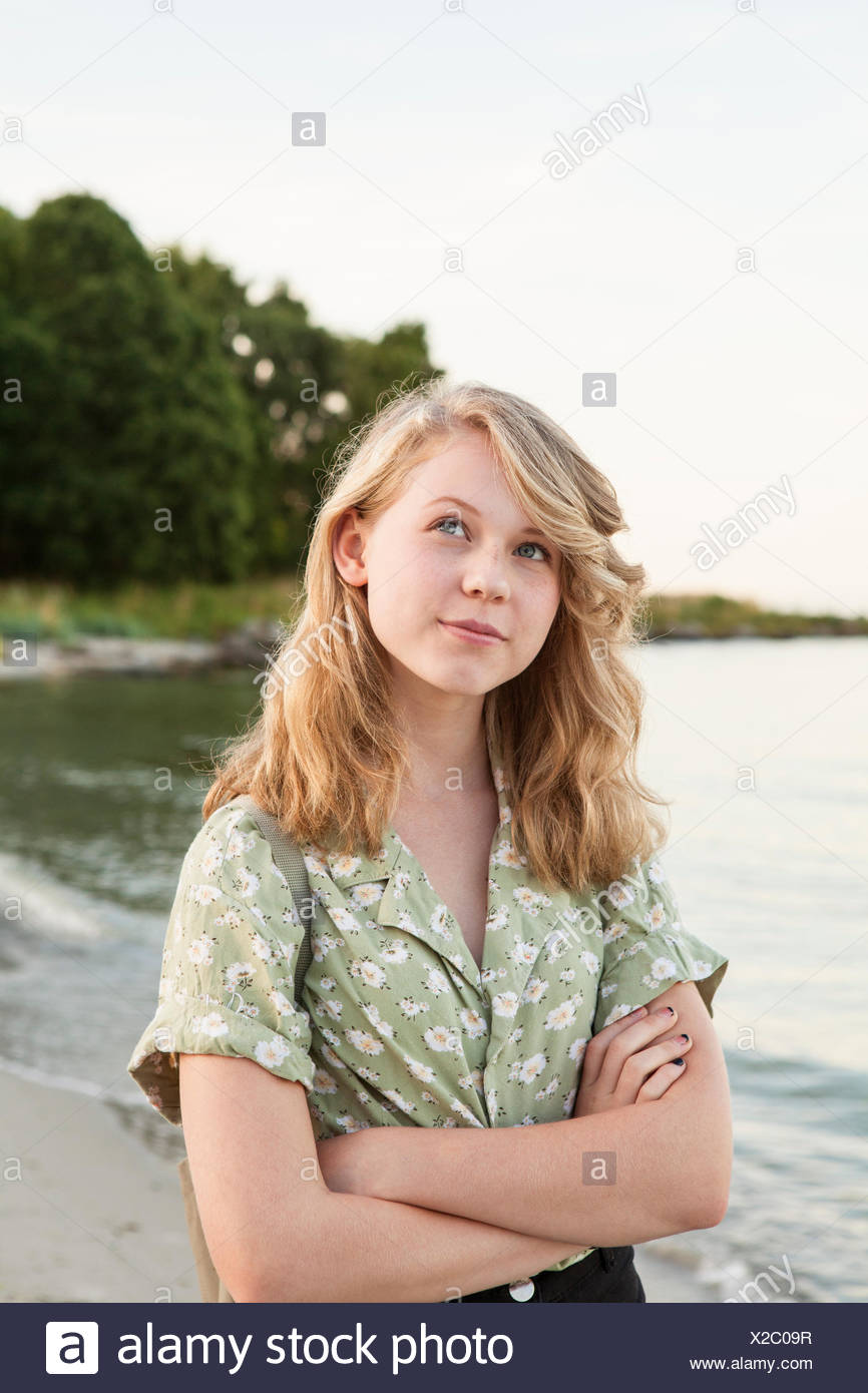 Sweden, Blekinge, Hallevik, Portrait of teenage girl (16-17) standing on beach - Stock Image