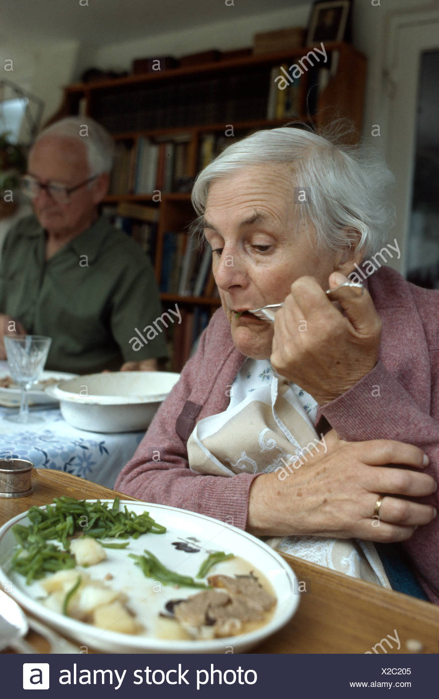 woman suffering with motor neuron disease struggles with her fork as she feeds herself - Stock Image