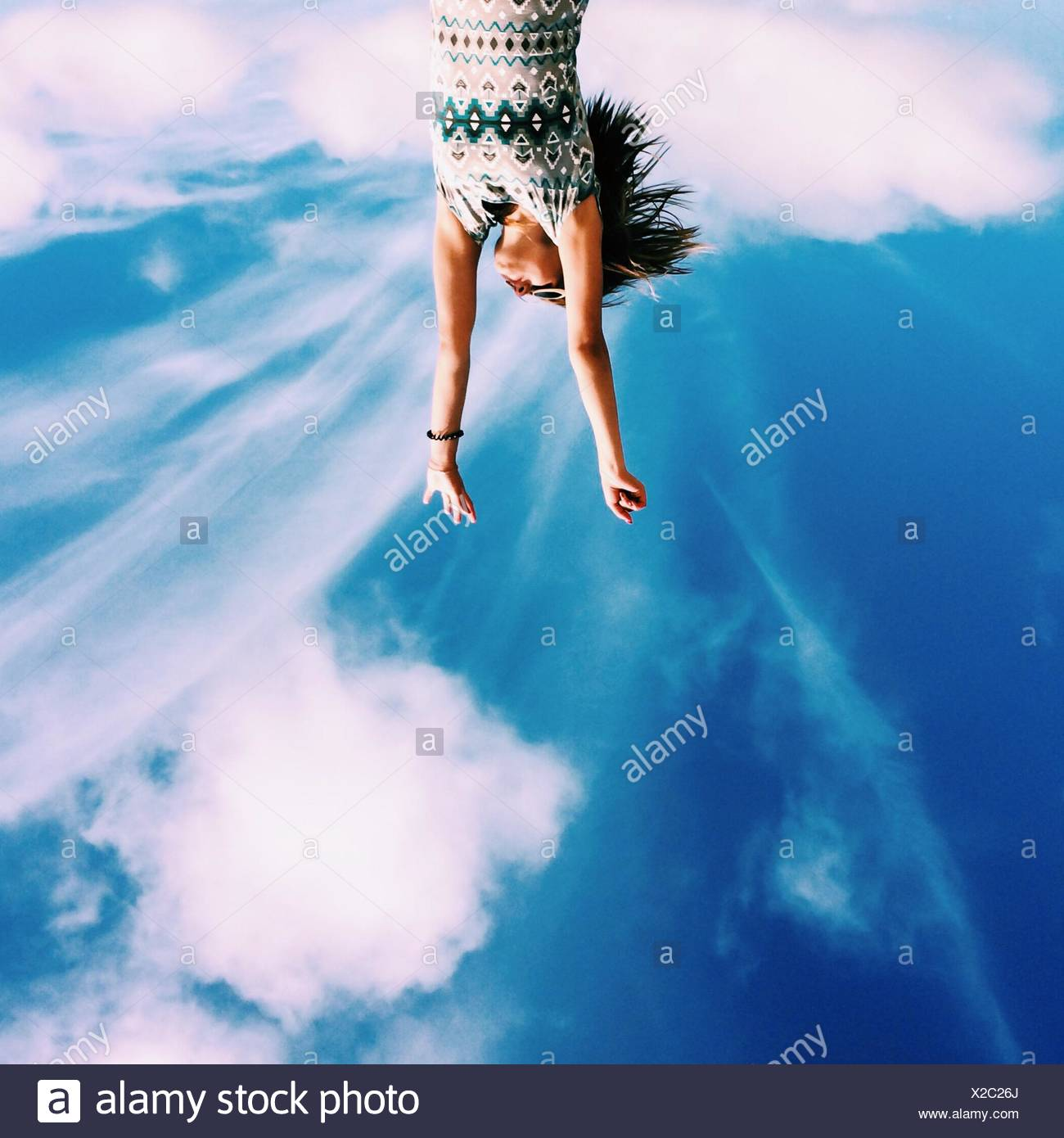 Upside Down Image Of Young Woman With Arms Raised Against Sky - Stock Image