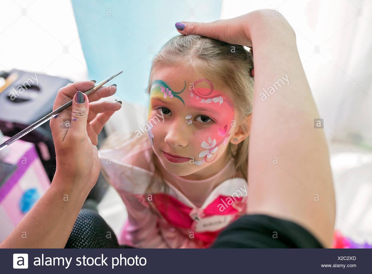 Little girl having her face painted - Stock Image