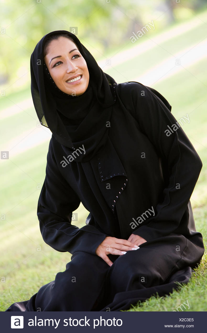 Woman sitting outdoors in park smiling (selective focus) - Stock Image