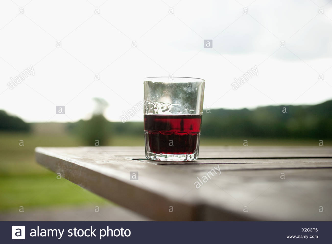 Drinks tumbler on picnic table - Stock Image