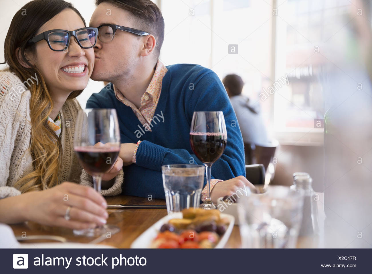 Couple with wine kissing in bistro - Stock Image