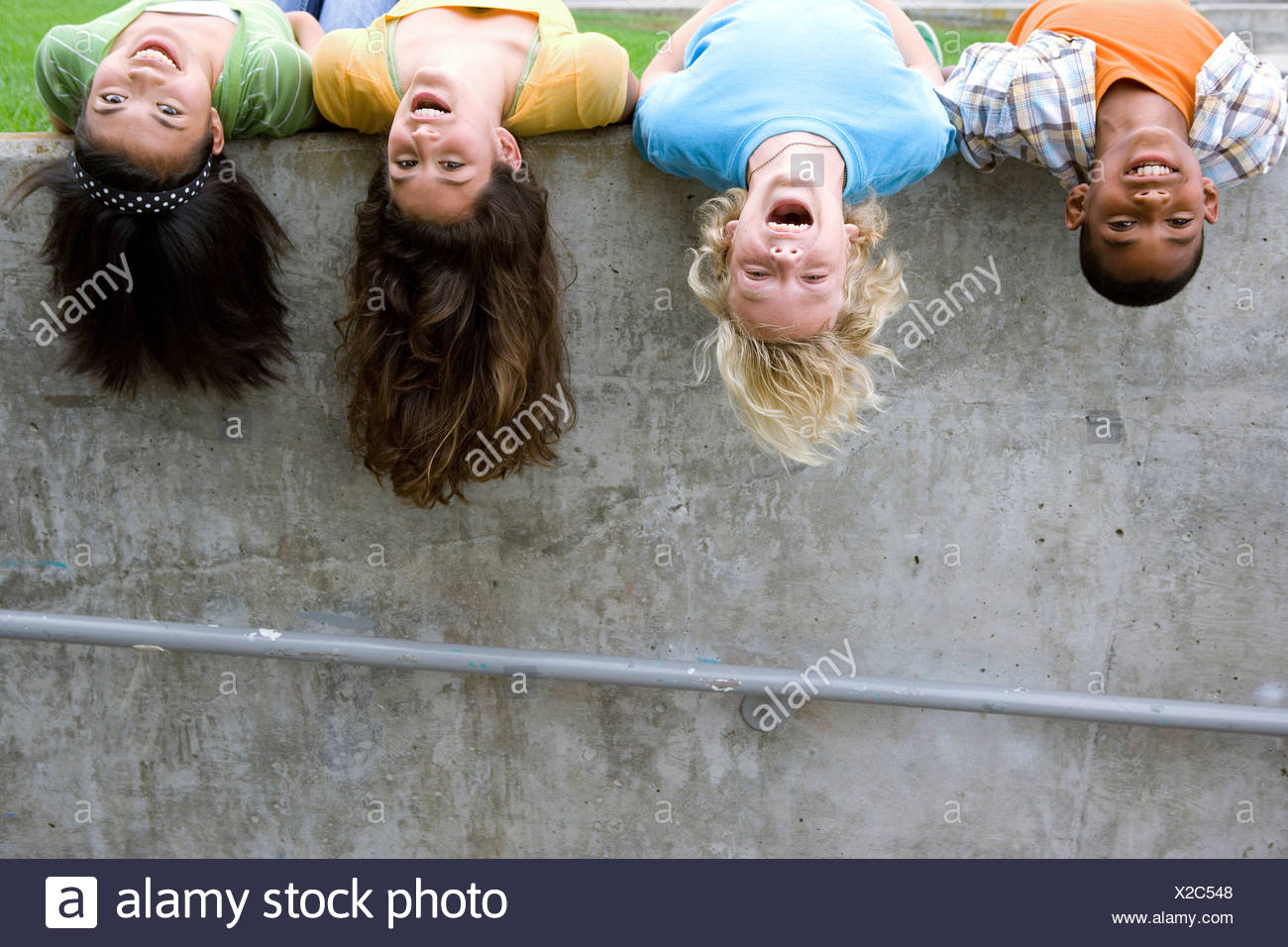 Small group of teenagers (13-15) hanging heads upside down off wall, portrait - Stock Image