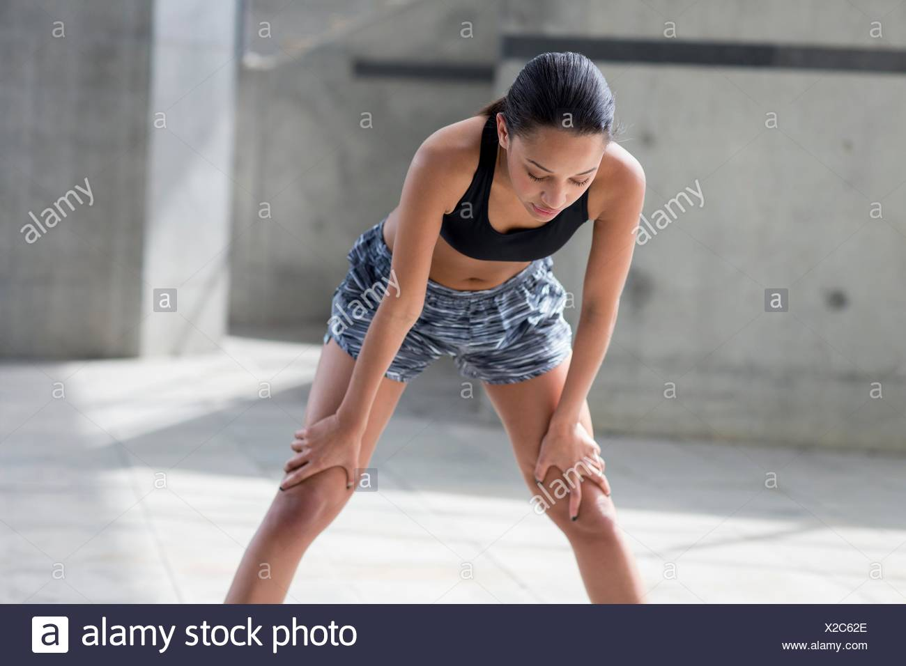 MODEL RELEASED. Young woman recovering after exercise. - Stock Image