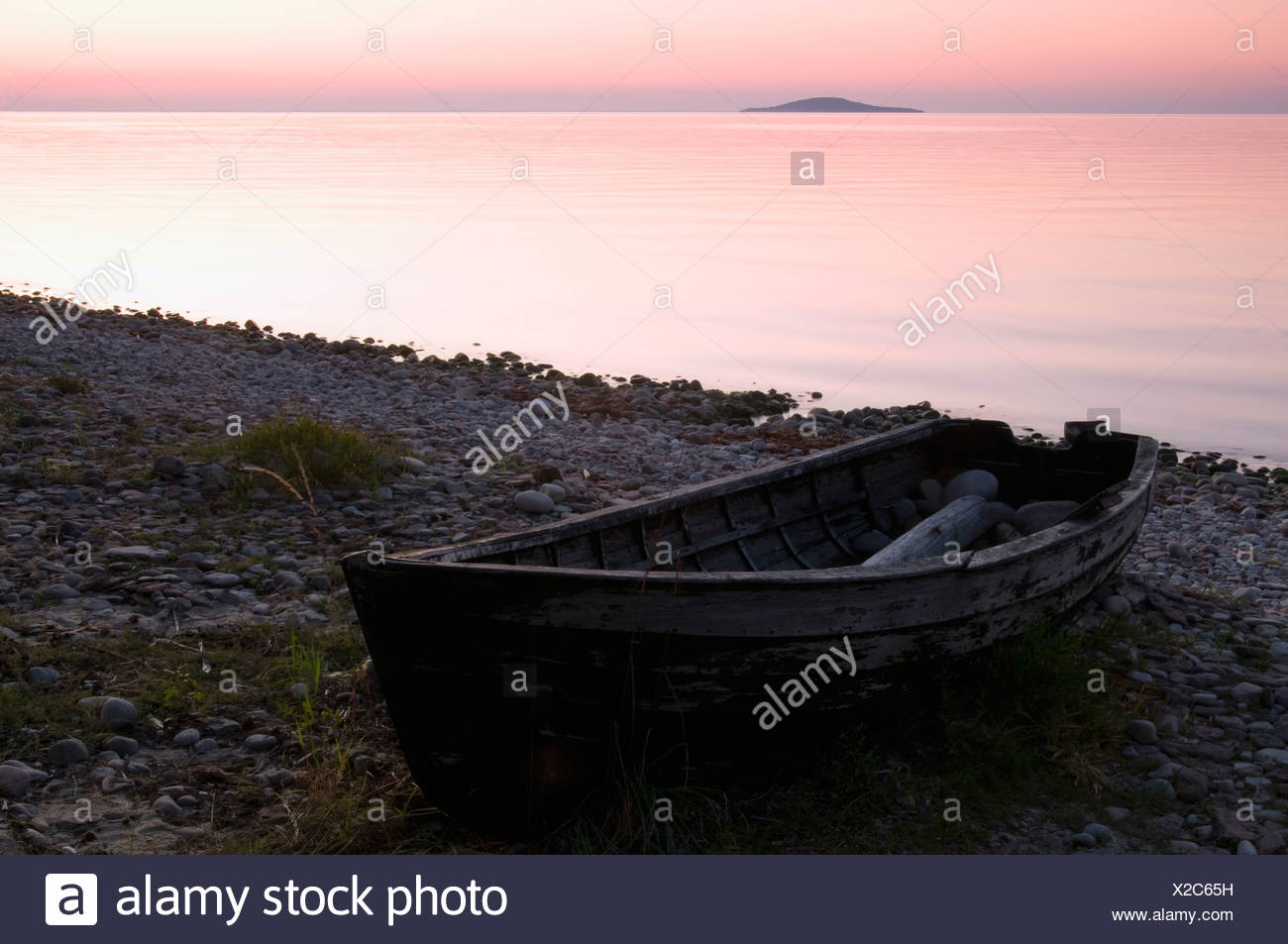 Row boat on shore at sunset - Stock Image