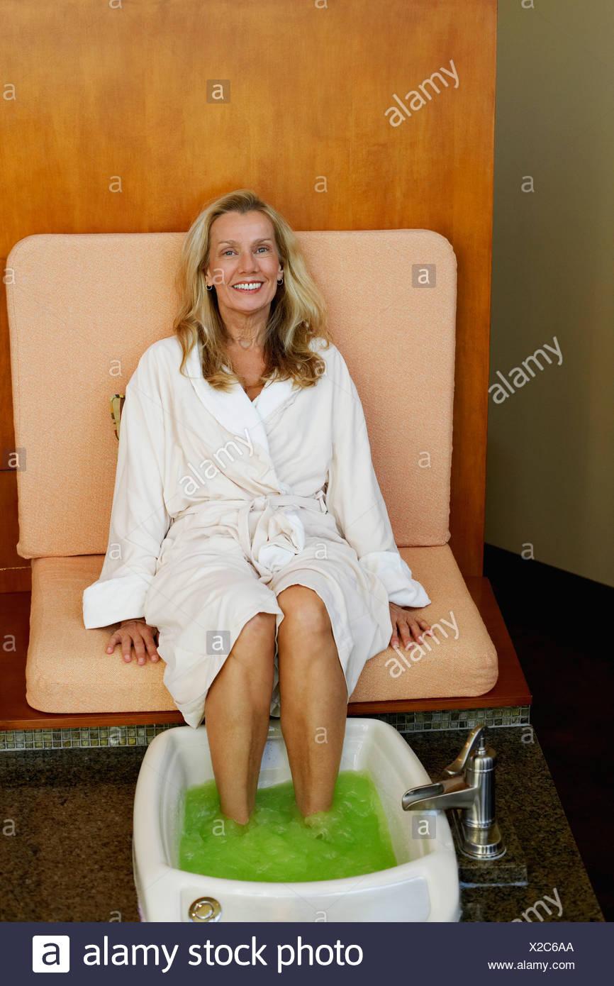 Portrait of a mature woman getting pedicure Stock Photo
