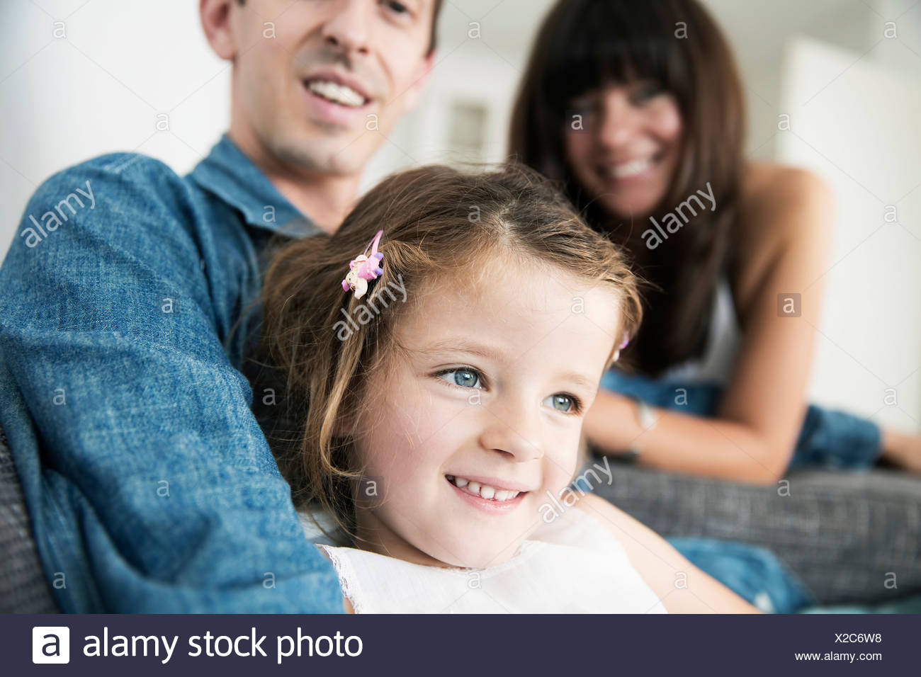 Young parents with little daughter sitting on sofa at home - Stock Image