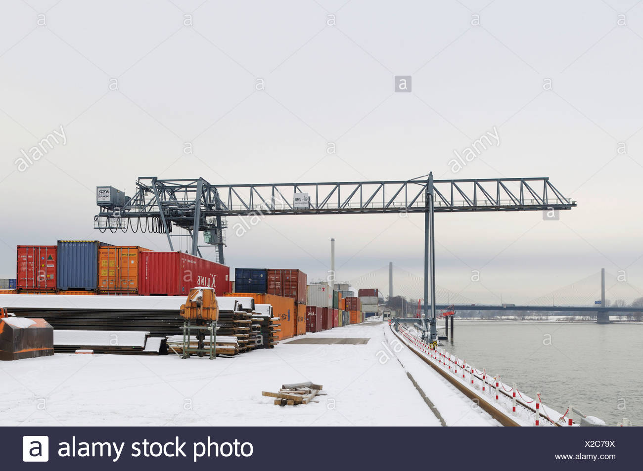 Winter at Bonn Harbour, snow-covered quay, view of container terminal and portainer on the Rhine river, North Rhine-Westphalia, - Stock Image
