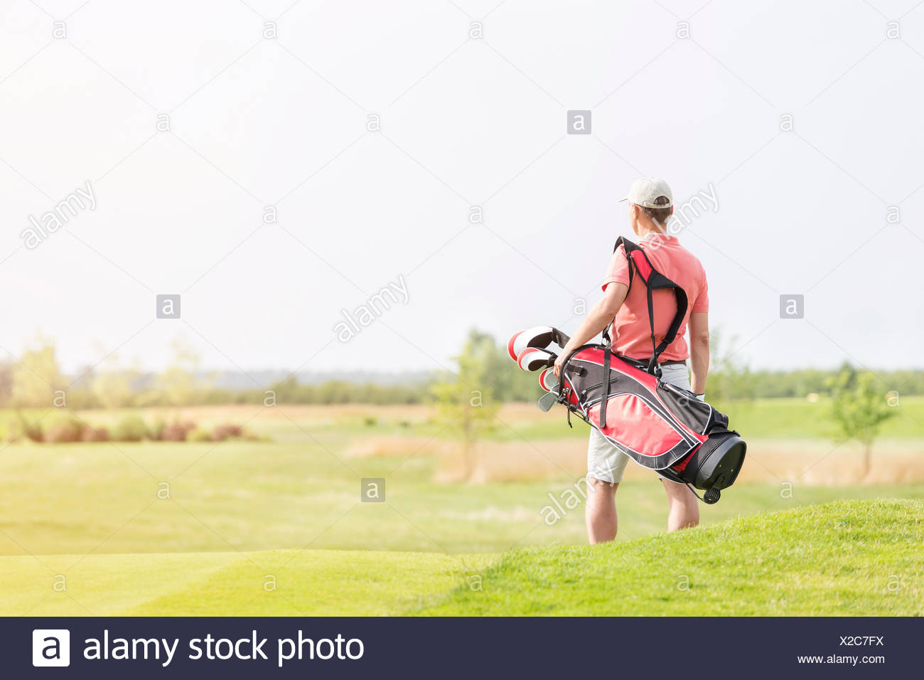 Rear view of man carrying golf club bag while walking at course - Stock Image