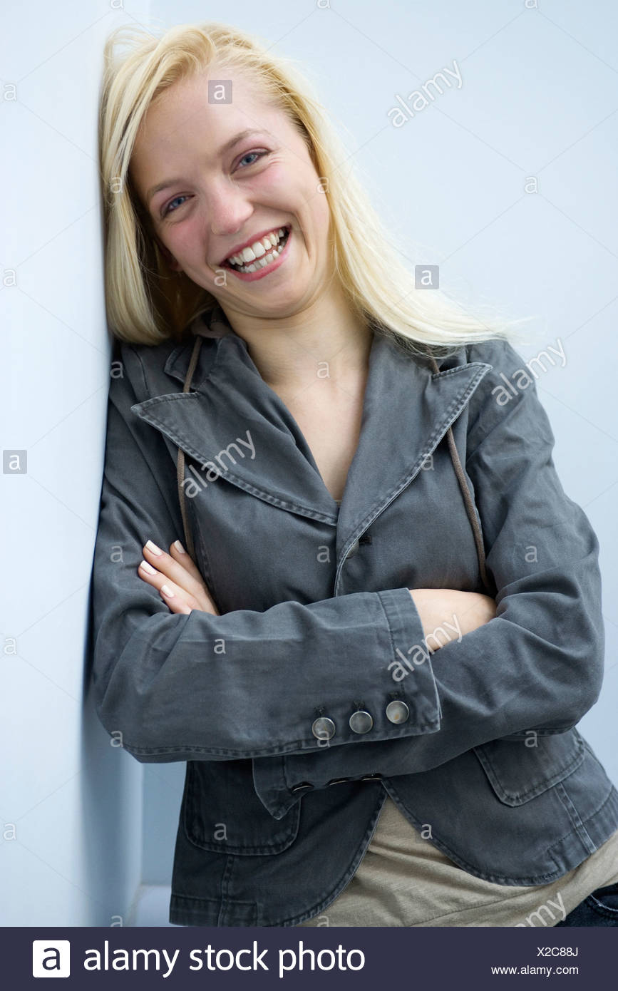 Young woman leaning against wall, smiling, portrait - Stock Image