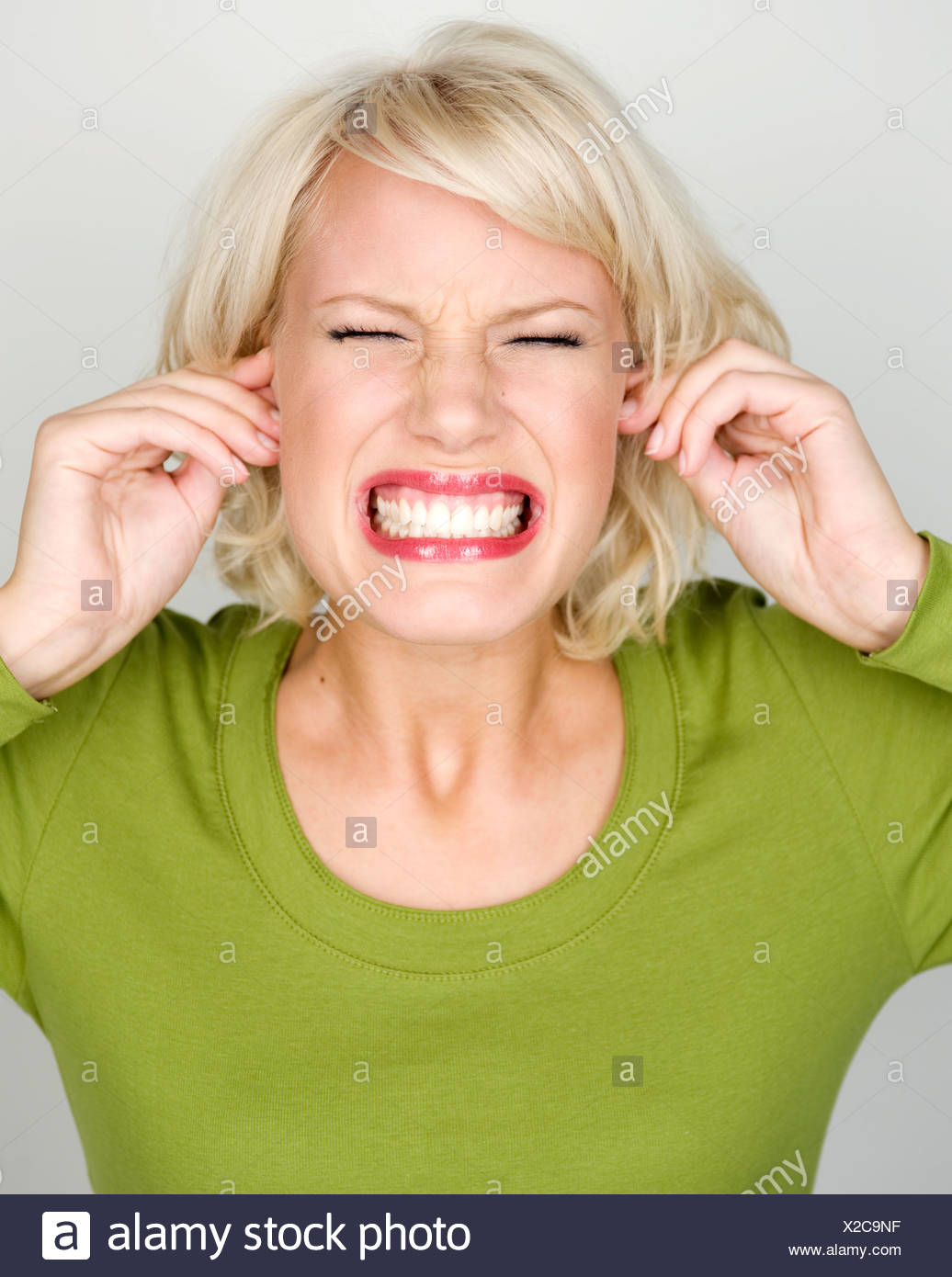 Female with her fingers in her ears and face screwed up - Stock Image