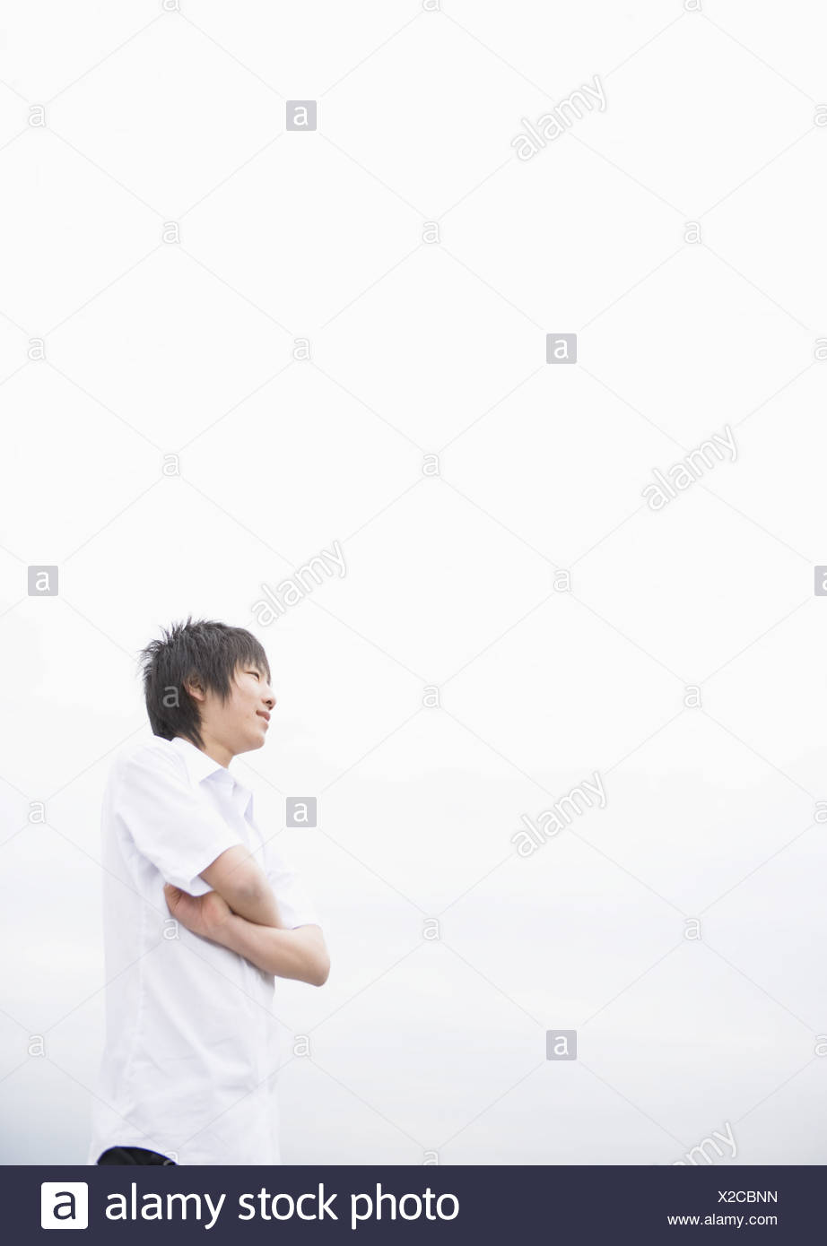 Teenageboy looking far with crossed arms - Stock Image