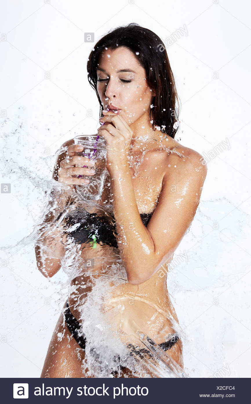 Young woman in bikini, being splashed with water - Stock Image