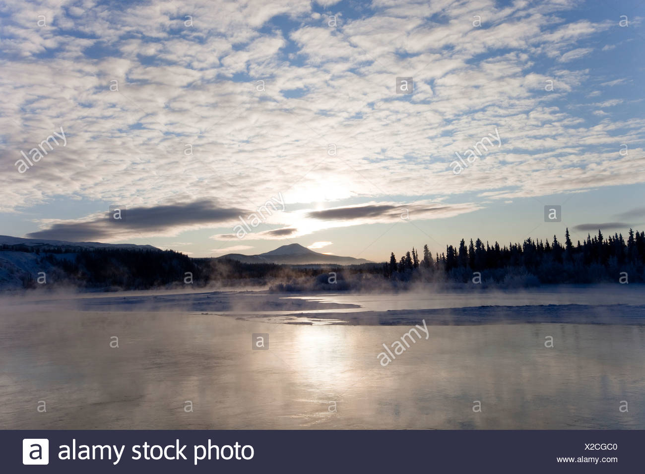 Ice fog, freezing, steaming, Yukon River, Golden Horn Mountain behind, near Whitehorse, Yukon Territory, Canada - Stock Image