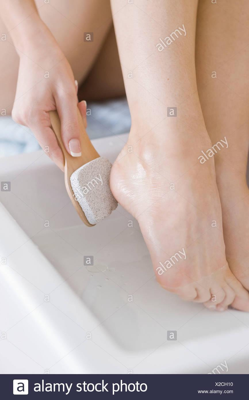woman using feet pumice - Stock Image