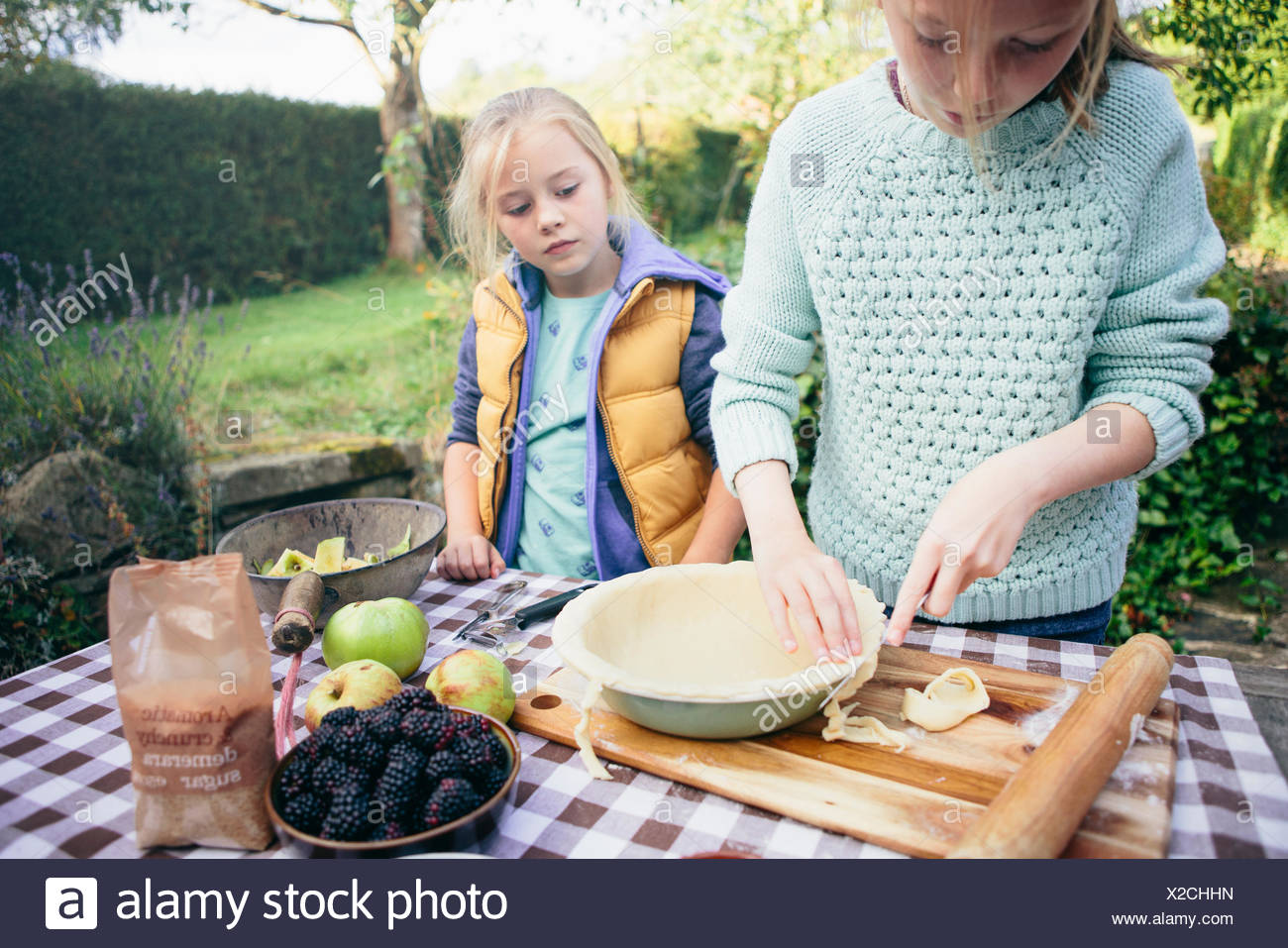 Two girls making a pie - Stock Image