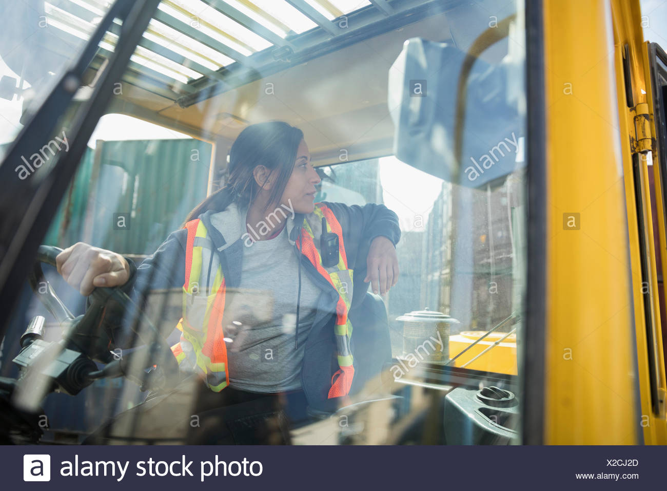 Female forklift driver inside forklift in industrial container yard Stock Photo