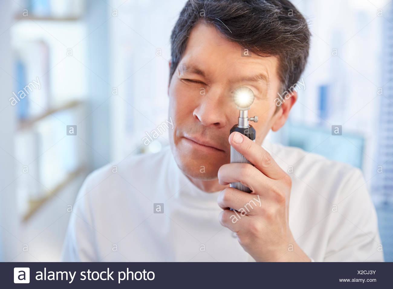 Man looking through illuminated speculum in laboratory - Stock Image