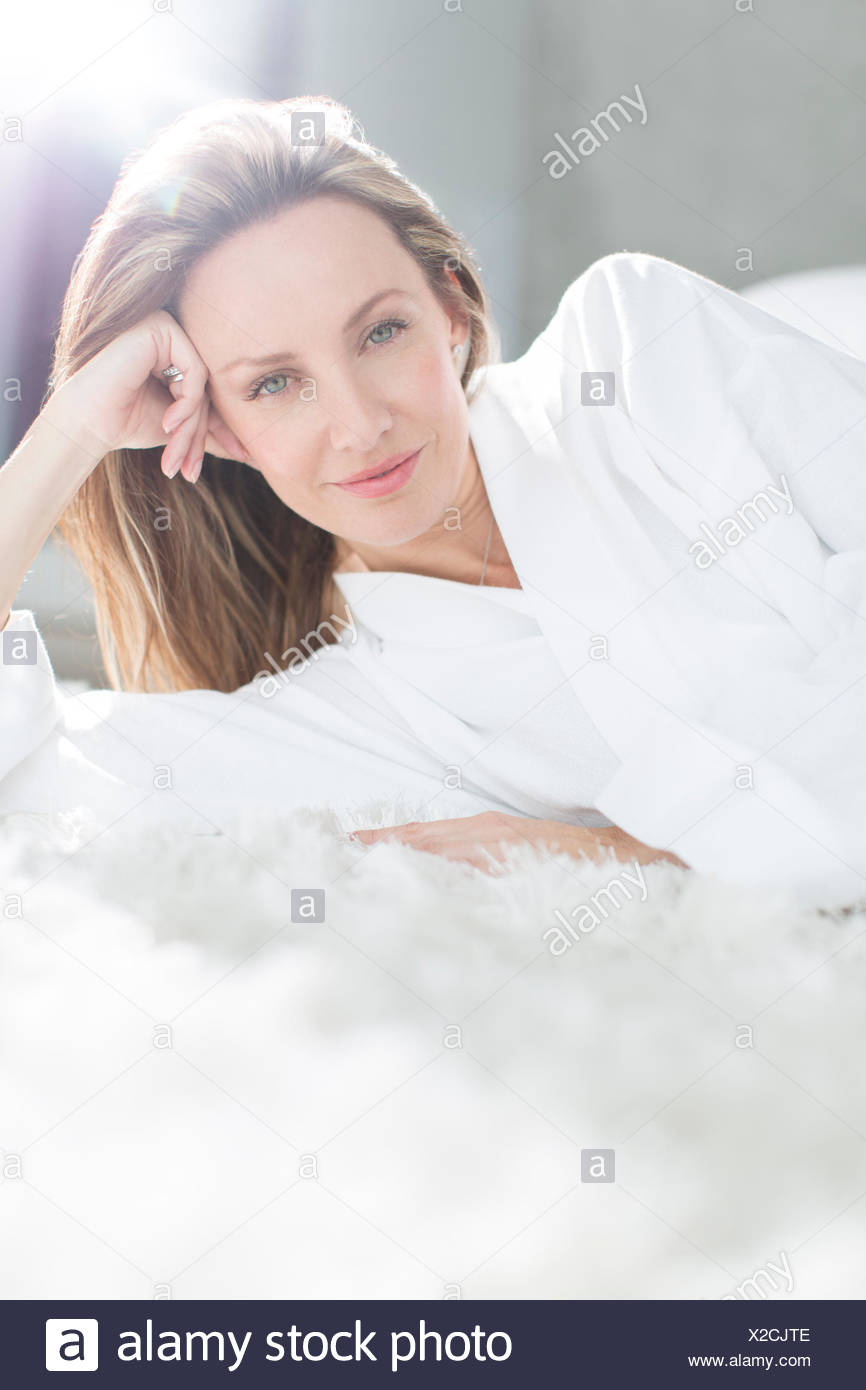 Woman in bathrobe laying on bed - Stock Image