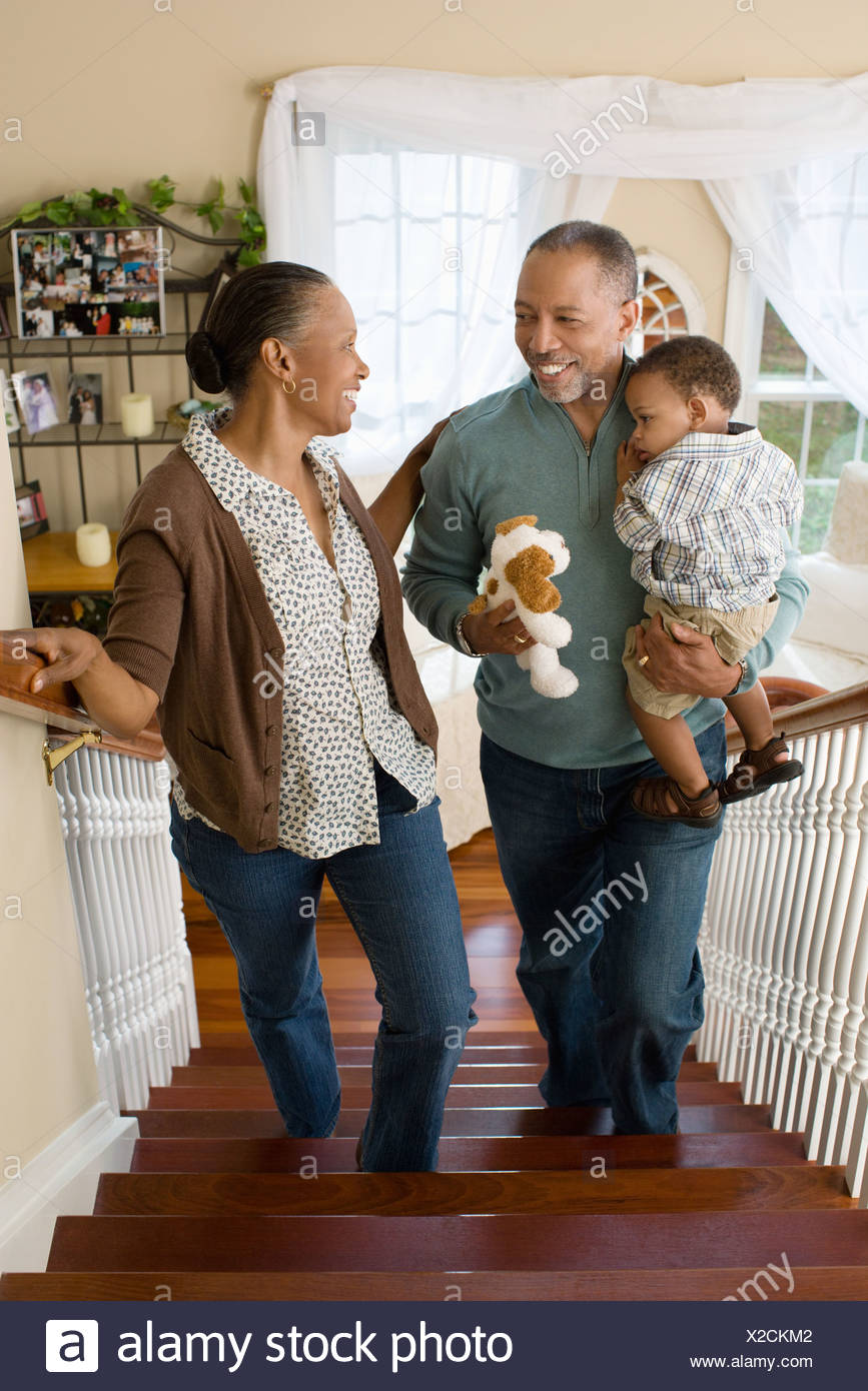 Grandparents carrying their grandson upstairs - Stock Image
