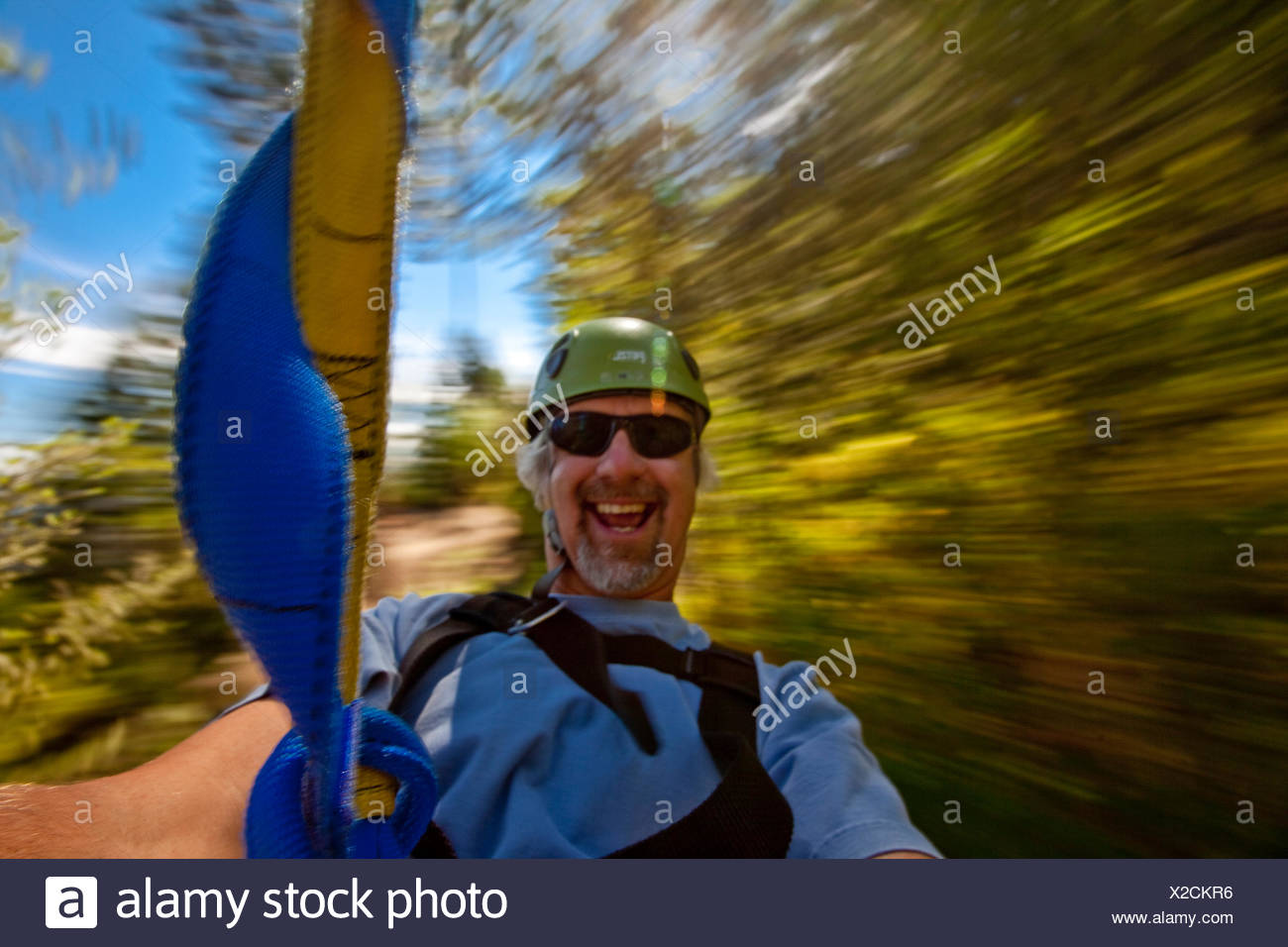 Man enjoys zip-line at Oyama Zipline, Okanagan Valley, BC, Canada. - Stock Image