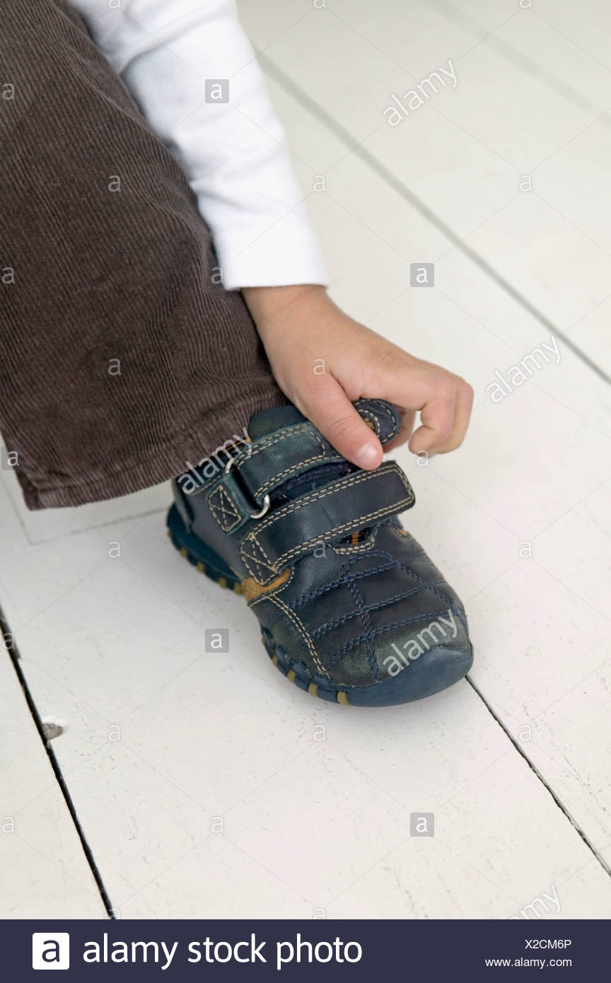 Boy's hand fastening shoe, close up - Stock Image