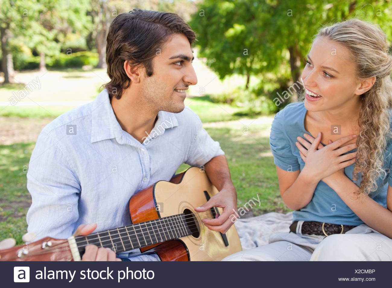 Male playing the guitar to impress his girlfriend - Stock Image