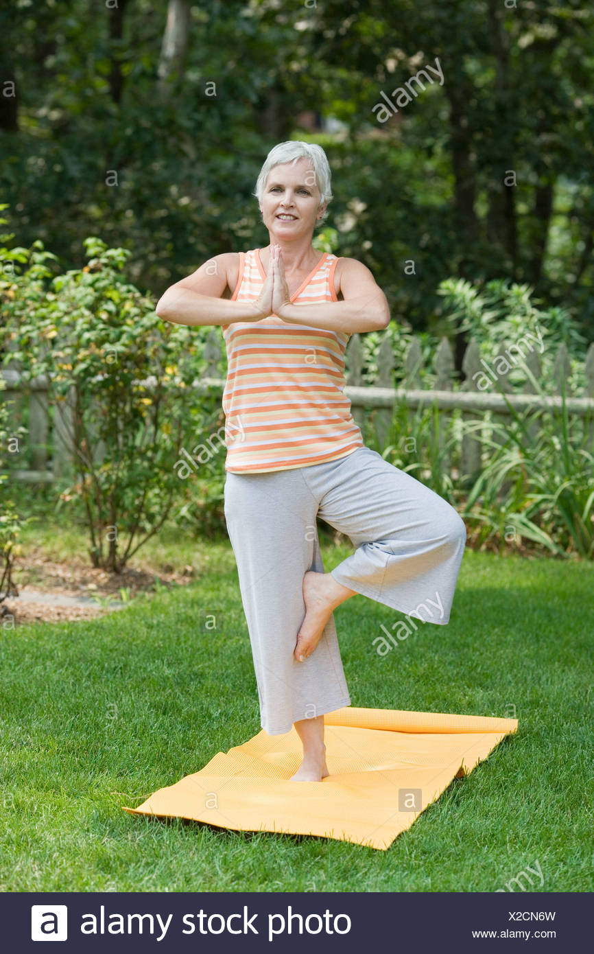 Mature woman standing on one leg in a park - Stock Image