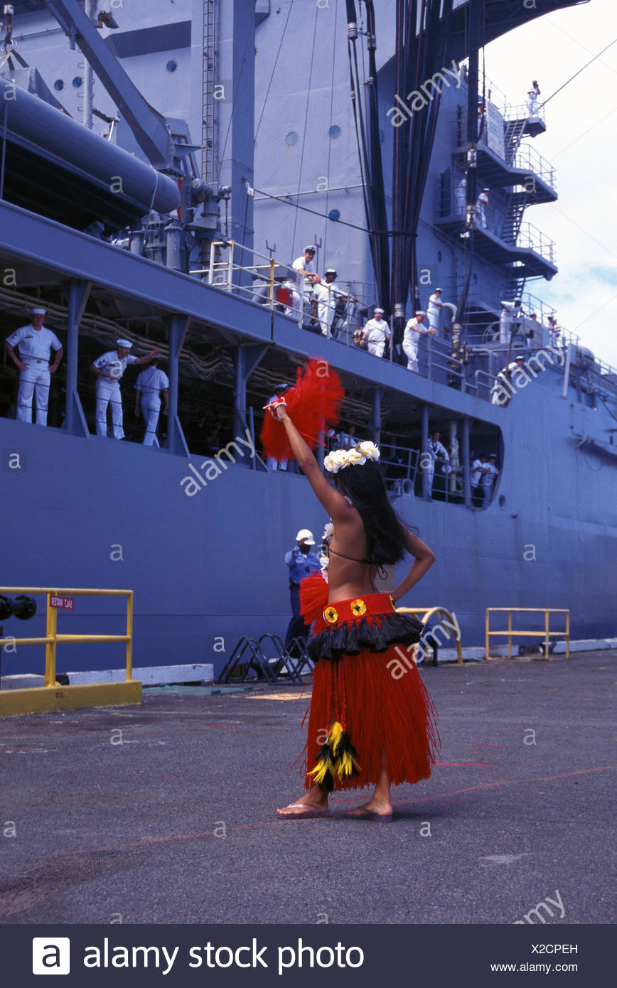 A hula dancer performs for sailors returning to Pearl Harbor after a long journey at sea. - Stock Image