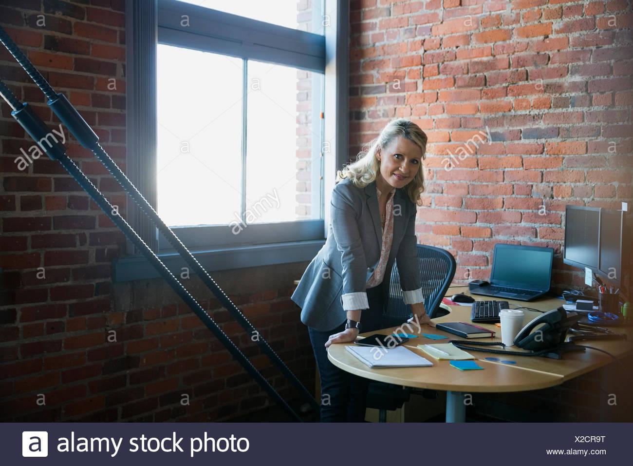 Portrait confident businesswoman leaning on desk - Stock Image