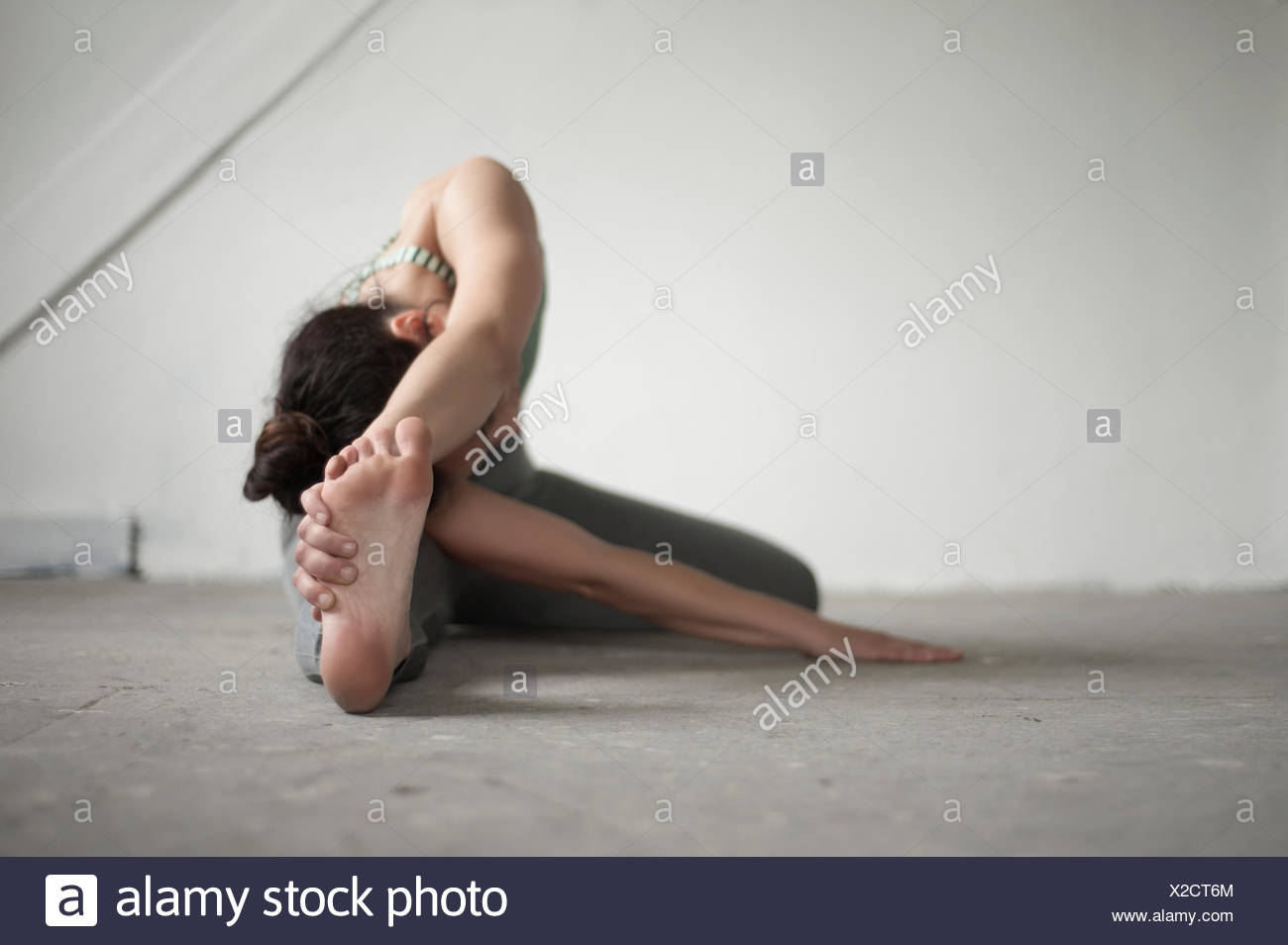 Mid adult woman practicing janu sirsasana pose in yoga studio, Munich, Bavaria, Germany - Stock Image