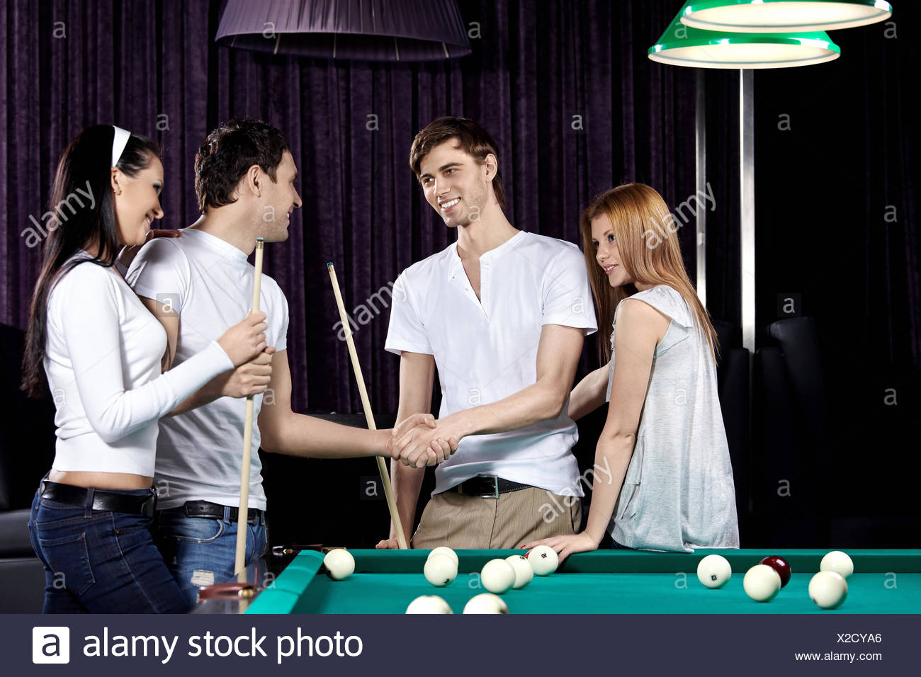 Young people with cue at a billiard table - Stock Image