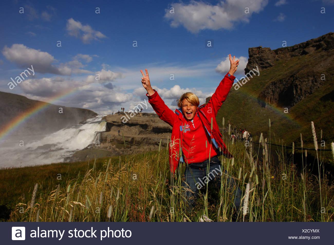 Child jubilating under rainbow on Gullfoss, The Golden Waterfall, Iceland, Europe Stock Photo