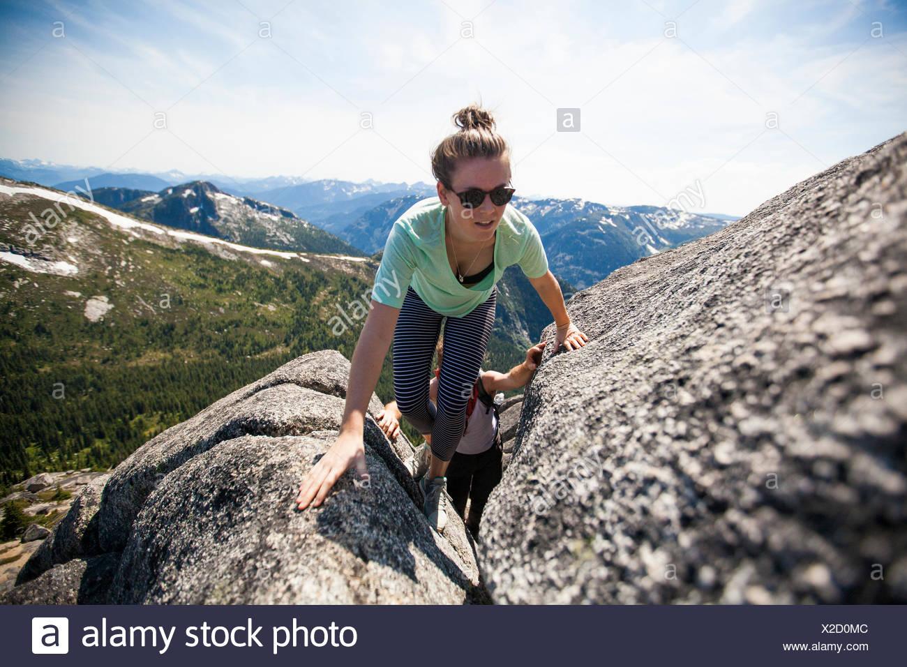 A man and woman scrambling up granite rock. - Stock Image