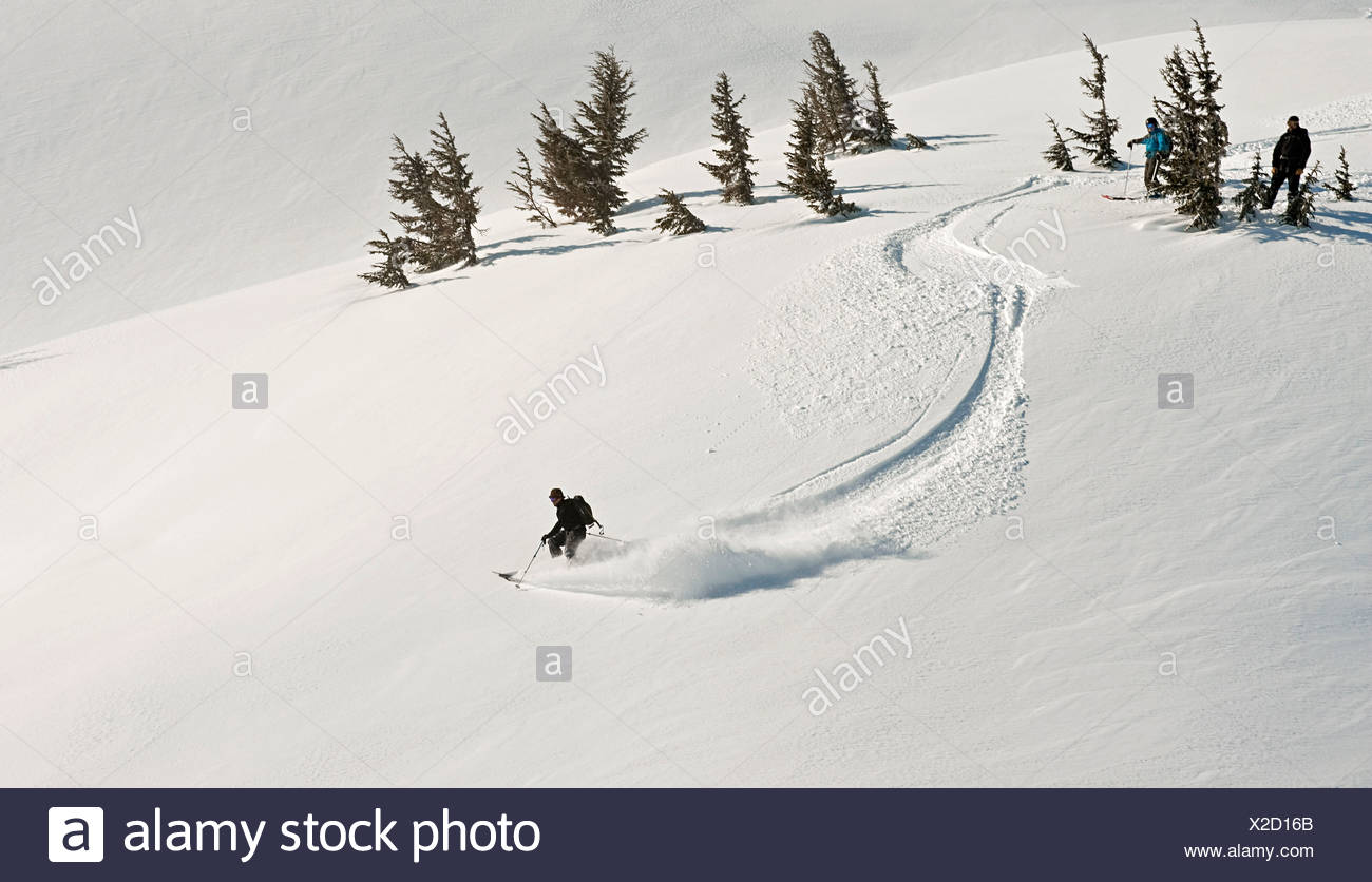 A skier and snowboarder watch as a fellow backcountry skier starts a descent in Turnagain Pass, Alaska - Stock Image