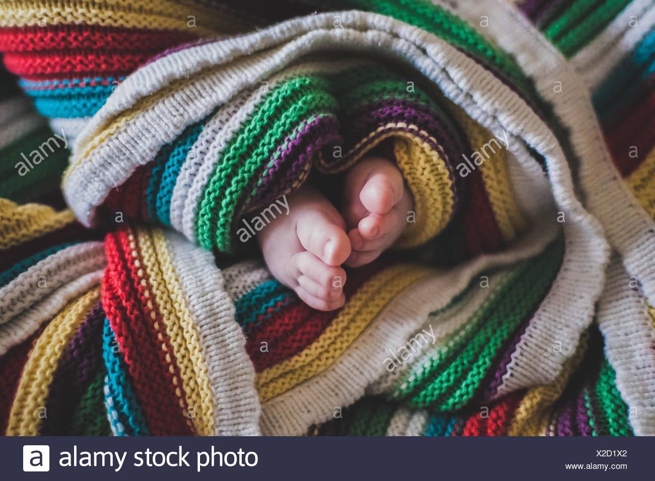 Close-up of baby's feet wrapped in a multi-colored blanket Stock Photo