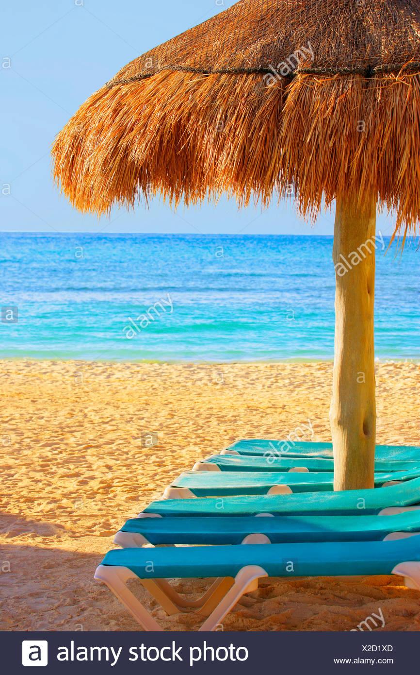 Grass hut loungers on beach - Stock Image